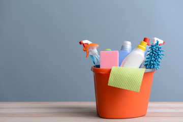 Set of cleaning supplies on table against color background Wall mural