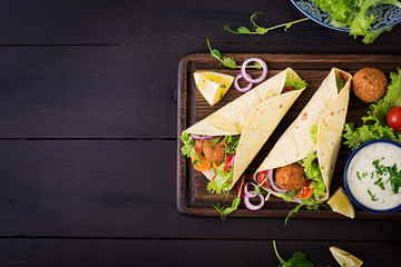 Tortilla wrap with falafel and fresh salad. Vegan tacos. Vegetarian healthy food. Top view Wall mural