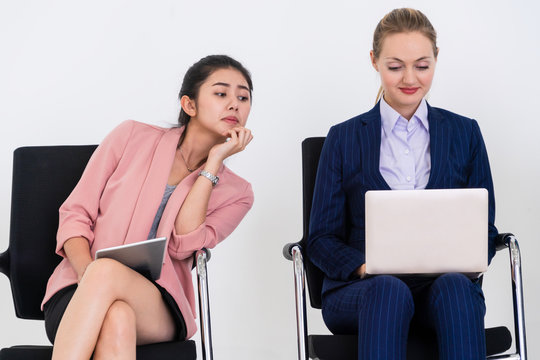 Curious businesswoman looking at the screen of laptop computer of another businesswoman spying stealing idea and copying private information from coworker at workplace. Plagiarism concept.