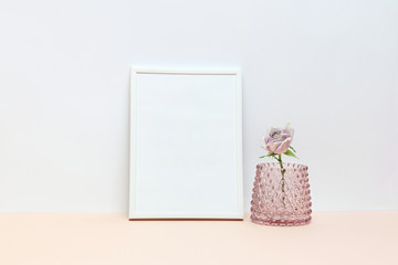 White frame with pink rose in a vase