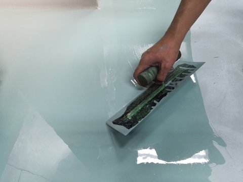Construction workers are painting the floor using the method self-leveling epoxy.spreading self leveling compound with trowel.Self-leveling epoxy. Leveling with a mixture of cement floors.