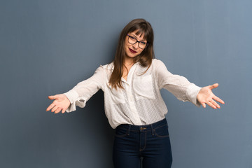 Woman with glasses over blue wall presenting and inviting to come with hand