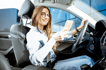 Young and cheerful woman using smart phone while driving a modern car in the city