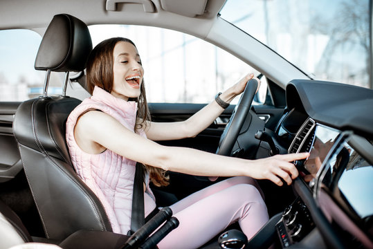 Young and cheerful woman in pink sportswear listening to the music while driving luxury car in the city