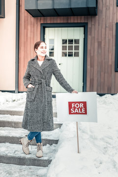 Beautiful stylish woman putting for sale sign near her house