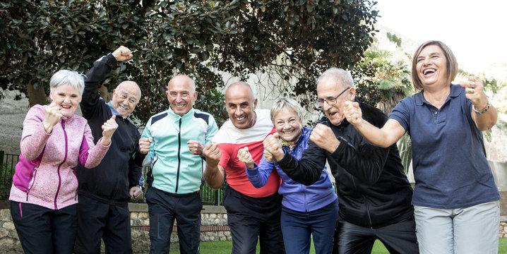 Gruppo di anziani signori vestiti in tuta si gode la vita al parco