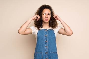 Dominican woman with overalls having doubts and thinking