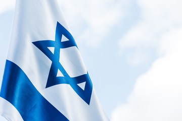national flag of israel with blue star of david against sky with clouds