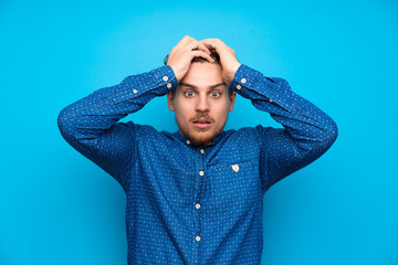 Blonde man over isolated blue wall with surprise facial expression