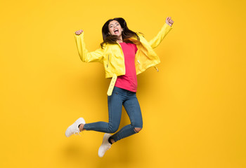 Teenager girl jumping over isolated yellow wall Wall mural