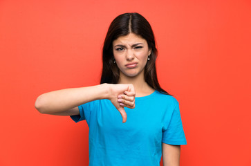 Teenager girl with blue shirt showing thumb down sign