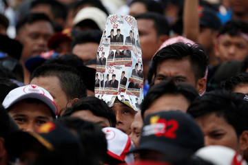 A supporter wears a hat made of pictures of Indonesia's presidential candidate for the next month election Prabowo Subianto, and his running mate Sandiaga Uno, during a campaign rally in Bogor