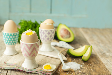Boiled eggs in holders with avocado on a grey wooden rustic table