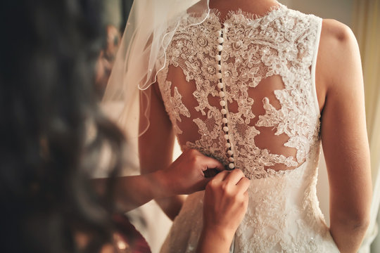 Bridesmaid helping bride fasten corset close-up and getting her dress, preparation concept in morning for wedding day.