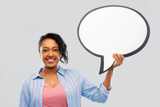 people and communication concept - happy african american young woman holding big blank speech bubble over grey background
