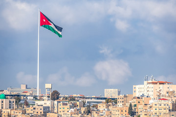 02/18/2019 Amman, Jordan, the flag of Jordan on the background of the gloomy sky walks in the wind above the capitals of the capital of the Middle Eastern state