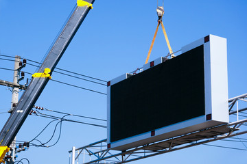 Construction site crane is lifting a led signboard Blank billboard on blue sky background for new advertisement Fototapete