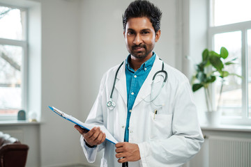 Indian doctor with stethoscope around neck in his office Wall mural