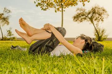 Brunette woman enjoying lying on her back on green grass in nature