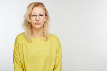 Serious European girl student in round glasses, yellow clothes looking into the camera, worried about entrance exams on a white background with copy space