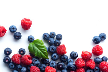 Raspberries and blueberries isolated on white background with copy space