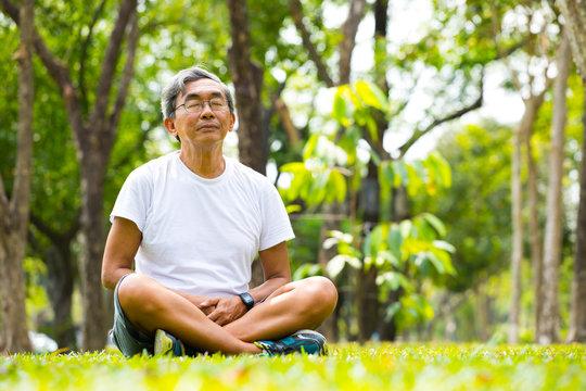 Old man Meditation in nature park