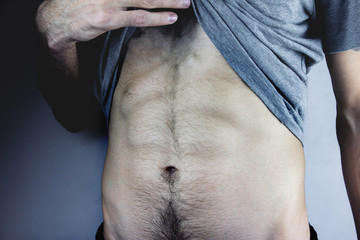 Acrylic Prints young man takes off his shirt