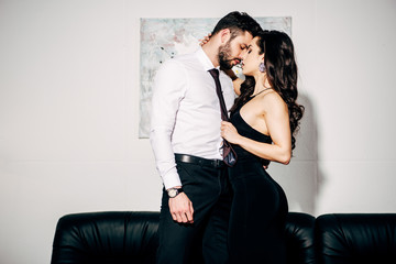 beautiful girl in black dress kissing handsome man in suit