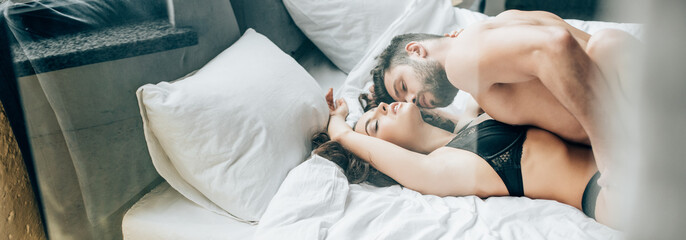 panoramic shot of bearded shirtless man kissing passionate brunette woman on bed