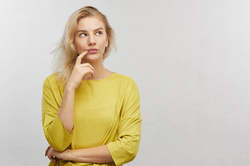 Portrait of embarrassed young woman looks aside holds chin with confused mouth in yellow clothes on white background with free space for your text