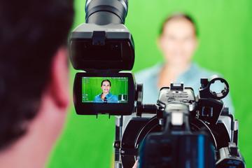 Kamera auf eine Nachrichtensprecherin oder Reporterin gerichtet bei einer Aufnahme im Studio