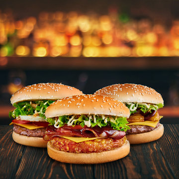 three burgers at brown wooden tabletop with blurred bar at backdrop . Fastfood concept with hamburgers at wooden table