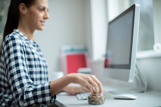 Female Worker In Office Having Healthy Snack Of Dried Nuts And Seeds