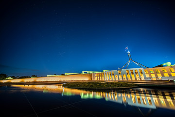 Facade of new parliament house in Canberra on capitol hill at sunset with bright illumination reflecting in blurred waters of pool.  South cross on sky