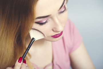Wall Mural - portrait of a beautiful young girl making makeup looking in a pocket mirror in a studio, woman dusting her face with a brush, cosmetics and beauty concept