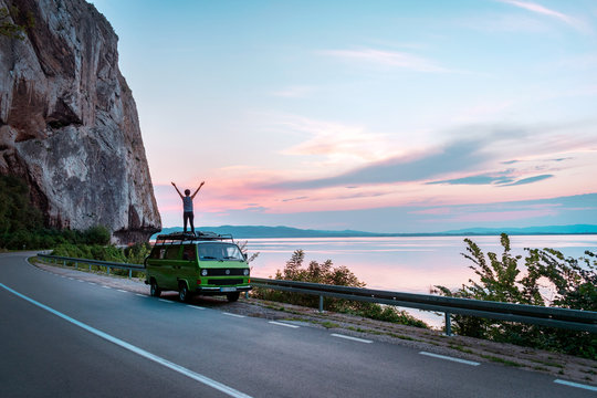 Young girl standing on top of vintage classic camper van with hands wide open. Freedom on the summer road trip beside seashore with beautiful sunset. - Image