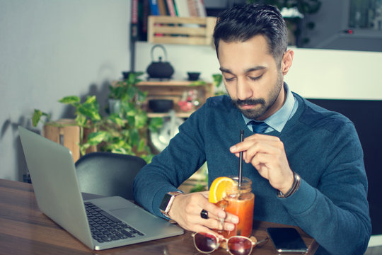 Young businessman working with laptop and drinking cocktail at office