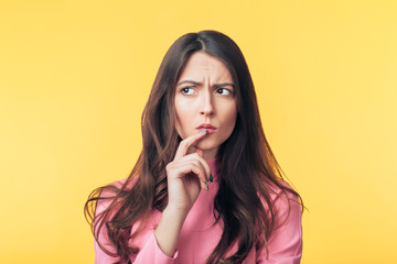 Thoughtful confused woman looking away isolated over yellow background