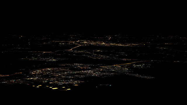 Lights of roads Amsterdam city top view from airplane window at night
