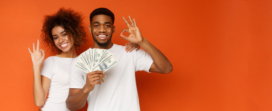 Cute black guy and girl holding money fan and gesturing ok