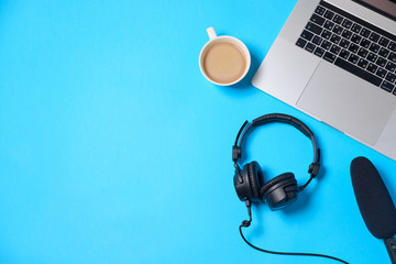 Music or podcast background with headphones, microphone, coffee and laptop on blue table, flat lay. Top view, flat lay