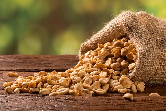 peanut in sack bag on wooden background