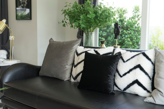 Close up gray pillows setting on beige couch in living room