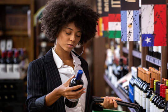 African business Woman holding bottles of wine in supermarket