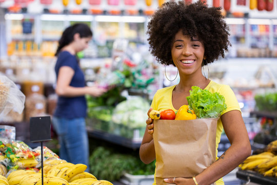Healthy positive happy african woman holding a paper shopping bag full of fruit and vegetables