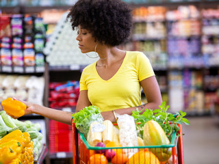 Healthy positive happy african woman holding a shopping cart full of fruit and vegetables.