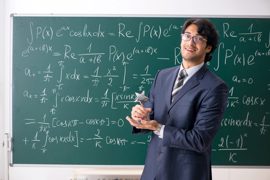 Young male math teacher in classroom