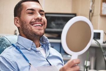 Your smile is our mission. Handsome male patient looking at his beautiful smile sitting at the dental office. Close up