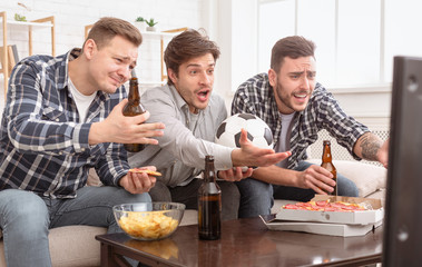 Disappointed friends watching football game, upset about loss