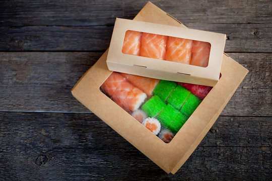 delivery service Japanese food rolls in cardboard box on a wooden background